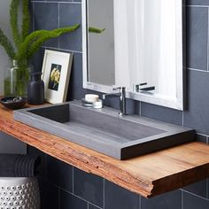 I love the mix of modern and rustic in this bathroom design. This Trough 3619 Bathroom Sink is by Native Trails and looks killer upon that live edge top. Tumbleweed Interiors LLC: