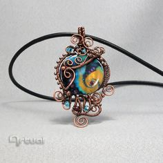 One of a kind hammered pendant wrapped with oxidized copper wire. The pendant is embellished with small copper beads, Japanese glass beads and a large,