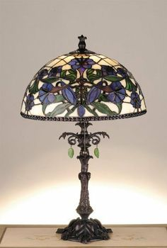 Victorian Nouveau Lily Accent Lamp by Meyda Tiffany. $446.40. 77714 Features: -Plum blue blossoms and buds, laced with green stems and leaves.-Ivory Tiffany style stained glass shade bordered with amethyst jewels.-Leaf and vine lamp base.-Hand painted in Mahogany Bronze.-Icy green leaf pendalogs.-Meyda designer original. Color/Finish: -Accent lamp. Specifications: -Accommodates: (1) 60W medium bulb. Dimensions: -Overall dimensions: 23'' H x 14.5'' W.