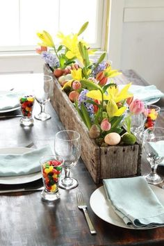 Easter eggs and flowers in a long vintage wooden box for a tablescape table setting centerpiece
