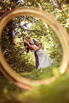 """From an article titled """"50 Must-Have Photos with your Groom""""...a photo through the weeding ring."""