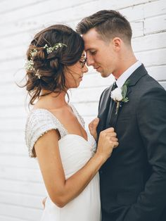 Messy wedding updo with braids and white wax flowers