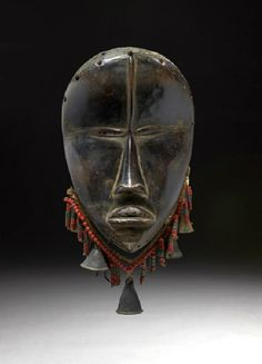 Africa | Mask from the Dan people of the Ivory Coast | Wood, brass bells and glass beads