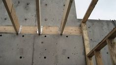 wood-floor-joists-attached-to-concrete-wall-through-wood-ledger