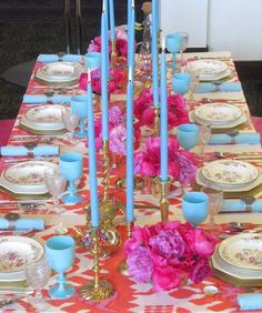 A spring table setting in orange, hot pink, and turquoise.