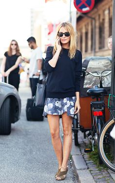 A navy blue sweater is worn with a floral skirt, sandals, a bucket bag, and Ray-Ban sunglasses
