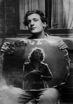 Ted Hughes holding a mirror with a reflection of his sister, Olwyn Hughes, as she takes his photograph. Undated.