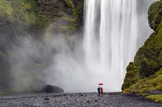 Two people holding an umbrella standing at the bottom of a large waterfall in Iceland.