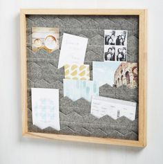 A wooden frame filled with layers of felt to display photos, postcards, ticket stubs, and other mementos on.