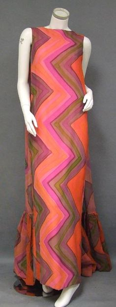 A STUNNING, dramatic Sarmi evening gown in a hot pink, bright orange, mauve and avocado printed silk chiffon. From the front it's a simple sheath... from the back it's pure glam. Two WONDERFUL wide shoulder scarves with gathered ends trail beyond the hem of the dress