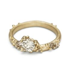 Unique asymmetric diamond engagement ring from Ruth Tomlinson featuring champagne diamonds in yellow gold, handmade in London.