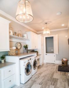 Laundry Room.  Laundry Organization.  White Built-in Cabinets. Front Load Washer and Dryer. Hardwood Tile Floor.