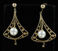 Southern Classic Jewelry - USA Period:1960 Material:14KT YELLOW GOLD Stones:PEARLS Condition:A FABULOUS PAIR WITH A MAJOR FLAIR! AN OPENWORK TRIANGLE OF 14KT YELLOW GOLD HAS A HANGING LENGTH OF 1 3/4 INCH AND IS GENEROUSLY LADEN WITH GOLD BEADS AND COMPLETED WITH A PEARL DANGLING IN THE CENTER. THE MORE YOU MOVE, THE MORE THE PEARLS SWAY CREATING BEAUTIFUL MOVEMENT ON THE EAR.  $1,295.00