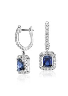Graceful and sophisticated, these drop earrings feature vibrant blue sapphires framed with a diamond halo set in 14k white gold.