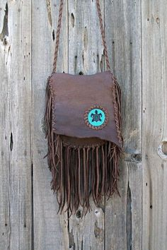 This Gypsy crossbody purse has tied fringe front and back and a beaded turtle totem on the front of the bag. This bag features an inside pocket and