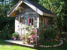 awesome garden shed, using recycled materials such as weathered wood, windows from an old milking barn, old rust hinges, old chair, old bear trap on the wall, old garden tools, old door, a rusty horse shoe to hook the door etc. I love this garden shed with all the old things being used!