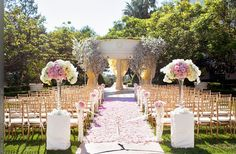 Lavender, pink, and white flowers with gold chiavari chairs for wedding ceremony.