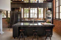 îlot central en métal et marbre gris à roulettes, tabourets en bois et métal et murs de briques exposées dans la cuisine style industriel