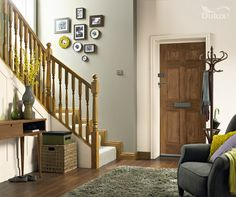 Olive green hallway with wooden doors and wooden bannister    Featuring Overtly Olive by Dulux.