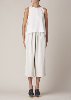 Pleated, wide-legged pants in off white cotton denim. Side slip pockets. Hook and bar closure with button reinforcement at side. Machine wash cold and tumble dry low or dry flat.