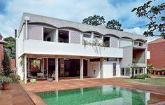 A casa, construída nos anos 1980, ficou atual com a reforma do arquiteto André Vainer. Ele integrou áreas interna e externa com painéis de correr de vidro, demoliu a edícula para aumentar o quintal e revestiu a piscina com pastilhas em tons de verde
