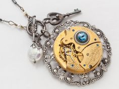 Steampunk Necklace Elgin gold pocket watch movement on silver filigree with blue crystal pearl skeleton key pendant jewelry  #SteampunkNecklace #SteampunkJewelry #SteampunkJewelrybyMariaSparks