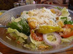 Olive Garden's Salad & Dressing Recipe 1/2 cup mayo,  1/3 cup white vinegar,  1 t vegetable oil,  2 T corn syrup, 2 T Parmesan cheese,  2 T Romano cheese,  1/4 t garlic salt or one clove garlic, 1/2 t  Italian seasoning  1/2 t parsley,  1 T lemon juice, sugar (optional) Romaine and ice berg, red onion, tomatoe, carrot, red cabbage, banana peppers, Parmesan, black olives, croutons