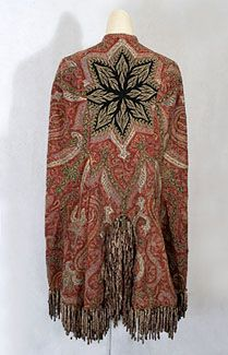 Hand-embroidered Kashmir shawl mantle, 1870s. The brilliantly hued mantle was fashioned from a hand-embroidered Indian Kashmir shawl. Lined with red satin and trimmed with variegated chenille fringe, the mantle closes in front with concealed hooks