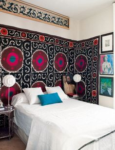 Suzani rug wrapped around the wall and serving as a headboard.