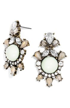 Glimmering crystals create a gorgeous halo around dreamy faux opals on these stunning drop earrings set in shining metal.