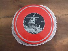 "Vintage Windmill Tin Round and Red by jessamyjay on Etsy. This bright vintage tin features the black and silver image of a windmill on the lid. There are tulips in the foreground and gulls flying in the sky. Nice silver striping on outer portion of the lid works well with the decorative image. Great decor piece or storage solution. Tins are also wonderful ways to ""wrap"" a gift with reusable packaging."