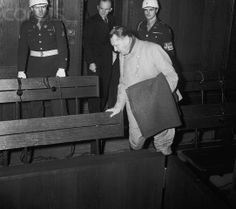 "Original caption: Goering Has the ""Sniffles."" Nuremberg, Germany: Hermann Goering, sporting a blanket because he suffers from a cold, enters the courtroom at Nuremberg for another session of the war crimes trial. Karl Doenitz is behind Goering. February 5, 1946."
