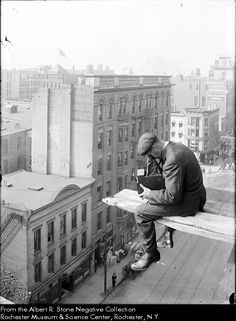 Albert Stone, photographer for the Rochester Herald newspaper, sits at the end of a long plank set 130 feet above the intersection of Clinton Avenue South and Main Street, from a building which is probably the Hotel Seneca,. He is looking through a camera at the street below him. This image is likely the result of trick photography. c.1907 Rochester NY