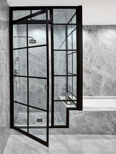 Inside an upgraded TriBeCa penthouse, a master bathroom features stainless-steel shower fittings and French marble