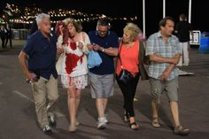 A woman whose shirt is covered in blood is helped after authorities said a truck slammed into a crowd in Nice, France, on July 14, 2016. French officials said more than 70 people were killed.