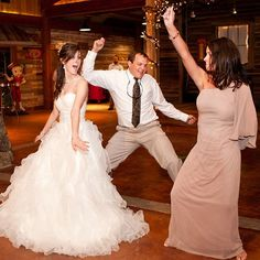 The newlyweds and a guest show off their dance moves! Photo Credit: John Mathis Photography