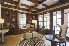 A paneled study with fireplace and built ins over looks the patio and pool area.