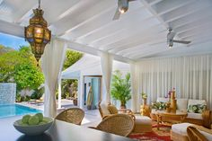An expansive covered porch has plenty of room for couches, sofas and a dining area. Pull the curtains for added shade or privacy.