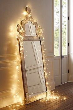 Drape a mirror with twinkling Christmas lights for a cheap, but elegant decoration in your apartment.