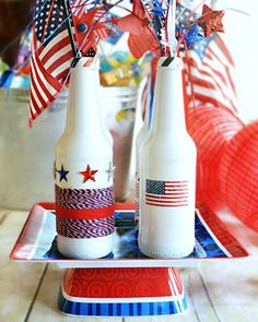 Empty glass bottles can become a patriotic centerpiece with paint, stickers, twine, and washi tape.