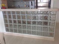 Decidimos colocar bloco de vidro na bancada.... Pensamos em varias coisas para substituir o concreto...imagine as pessoas na banqueta e os pezinhos encostando na parede? Não ia dar certo... Então optamos pelos blocos de vidro... Eu amei o resultado...achei que ficou esteticamente bom e funcional... Sem contar a claridade!