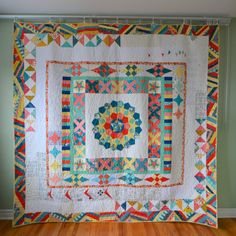 "Last year, I joined a ""traveling quilt"" bee - sometimes known as a ""round robin."" The idea is that you make your first block, then send it to the next person who adds to it. Then the person after adds to that, and so on (we had 11 people). At the end and comes back to you, all finished … I got mine back last week!   I can't even believe it's mine… it is so fantastic!   It started with the centre English paper pieced medallion that I made back when I was still living in Edmonton.    Deanna…"