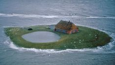 Hallig Habel, a farm in the flatlands of North Frisian Islands, Germany, during an extreme high tide. Handbuilt Shelter by Lloyd Kahn.