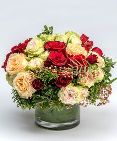 Festive Roses A wonderful collection of all red, green and white roses accented with pepperberry and seasonal greens.