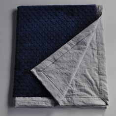 Gorgeous gray linen baby blanket! This adorable blanket is made from a light gray linen/cotton blend fabric and navy blue minky. Finished with mitered corners. Blanket measures approximately 32x37in.