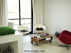 Muebles pequeños y cómodos hacen la diferencia. Se aprovecha y refleja la luz con las cortinas abiertas. La silla roja rompe el esquema y le da un toque de color al blanco departamento.