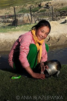 India, Ladakh. Angmo, 12-years old girl from Korzok washing the dishes in one of the streams.