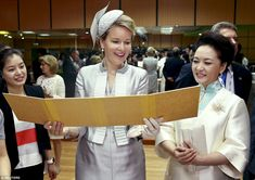 """Belgium's Queen Mathilde (C) and Chinese first lady Peng Liyuan (2nd R) look at a cartoon drawn by students featuring """"The Adventures of Tintin"""", a comic series from Belgium, as they visit a special school for deaf children in Beijing, China, June 24, 2015."""