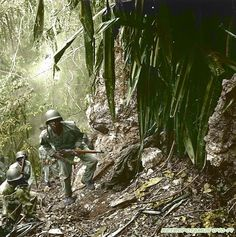 March 10, 1945: U.S. troops in the Pacific islands continued to find enemy holdouts long after the main Japanese forces had either surrendered or disappeared. Guam was considered cleared by August 12, 1944, but parts of the island were still dangerous half a year later. Here, patrolling Marines pass a dead Japanese sniper. These Marines may belong to the Fifty-second Defense Battalion, one of two black units sent to the Pacific. -
