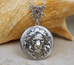 Photo locket with a lion on front cover. Photo locket features a 1 14 in diameter round vintage look locket with a silver lion stamping on front cover. The lion has been sealed with a clear resin to give a lasting glass like finish. Locket hangs on 22 silver plated chain with a